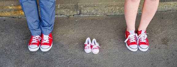 A picture of a couple with baby shoes